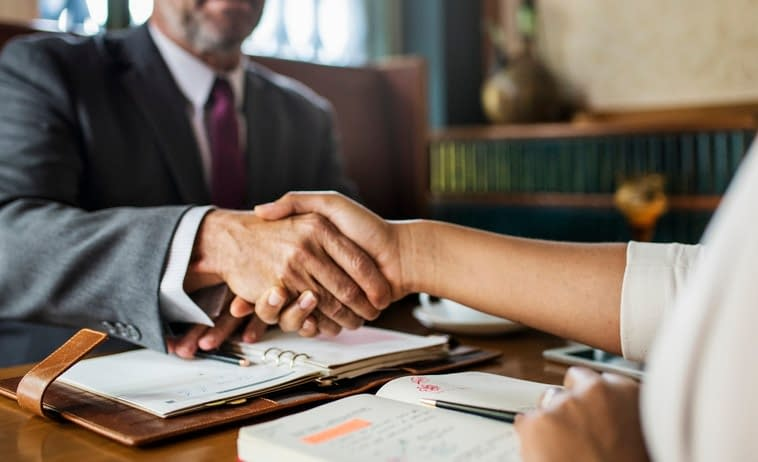Photo of attorney and clients shaking hands