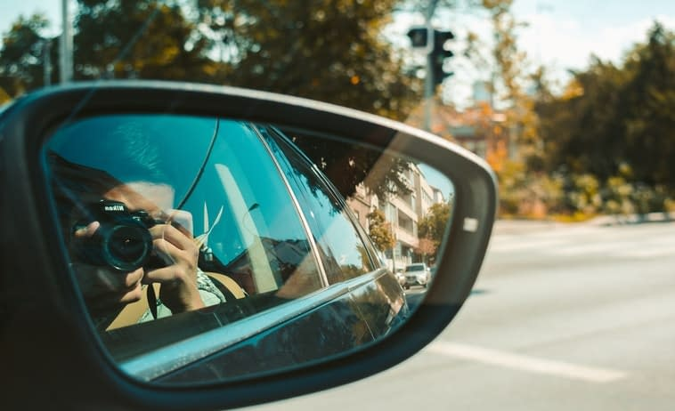 Photo of a car side mirror of a man taking a photo