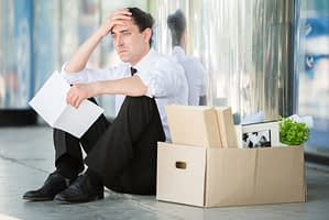 Upset man sitting with a box of belongings after being fired
